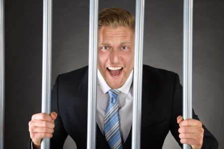 Portrait Of Aggressive Businessman Standing Behind Bars Stock Photo