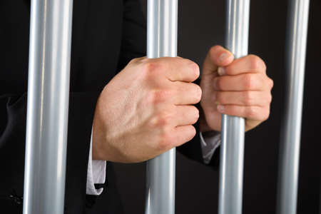 behind bars: Close-up Of Businessman Hand Holding Metal Bars In Jail Stock Photo