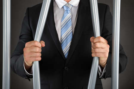 Close-up Of Businessman Hand Bending Bars Of Jail