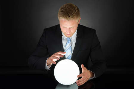 future vision: Retrato de hombre de negocios Predecir futuro con la bola de cristal Foto de archivo