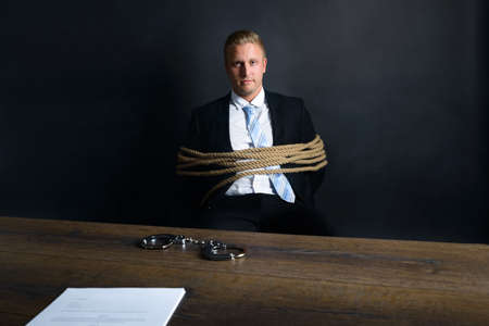 gagged: Portrait Of Young Businessman Tied With Rope Sitting In Front Of Table With Handcuff Placed On It