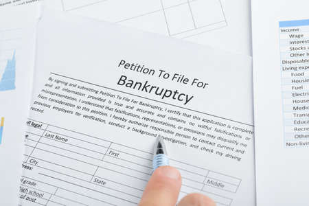 Close-up Of Hand With Pen On Bankruptcy Filing Petition Paper