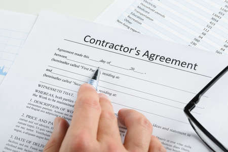 Close-up Of Hand With Pen And Eyeglasses Over Contractor Agreement Stock Photo