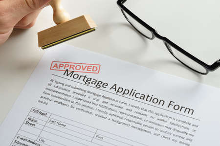 mortgage: Close-up Of Person Hand With Rubber Stamp And Red Approved Mark On Mortgage Application