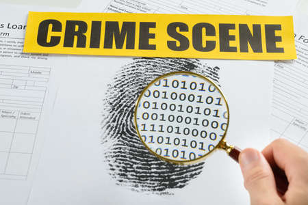 crime scene tape: Person Hand With Magnifying Glass Over Document Revealing Binary Code And Crime Scene Tape On It Stock Photo