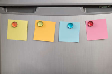 posted: Gray Refrigerator Door With Colorful Notes Posted With Magnets Stock Photo