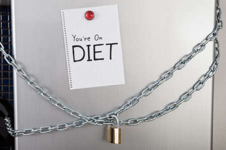 overeat: Diet Text On Note Posted With Magnet On Locked Refrigerator