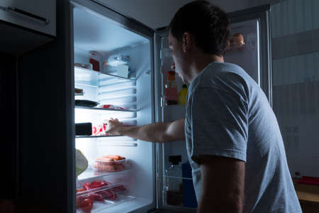 refrigerator with food: Portrait Of A Man Taking Food From Refrigerator