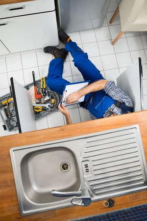 fontanero: Plomero Hombre Examinar fregadero en la cocina que sostienen el sujetapapeles