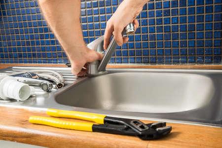 Close-up Of Plumber's Hand Fixing Tap Of Sink Foto de archivo