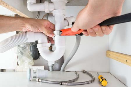 plumber tools: Close-up Of Male Plumber Fixing Sink In Bathroom