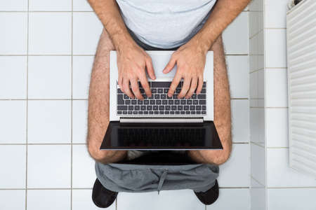 High Angle View Of A Man In Toilet Using Laptop photo