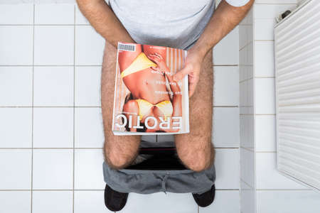 men sex: High Angle View Of A Man In Toilet With Sexy Magazine
