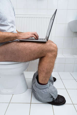 Close-up Of A Man Sitting On Commode Using Laptop photo