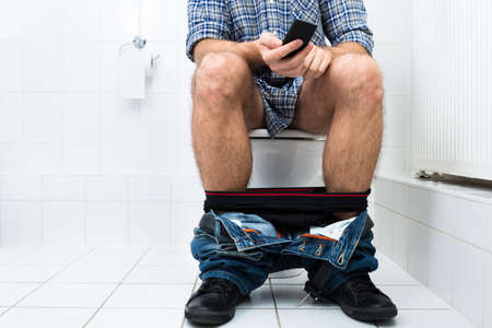a toilet seat: Close-up Of  A Man In Toilet Using Cellphone Stock Photo
