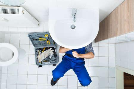 Opinión de alto ángulo masculino Plomero Reparación un lavabo en baño Foto de archivo - 35689919