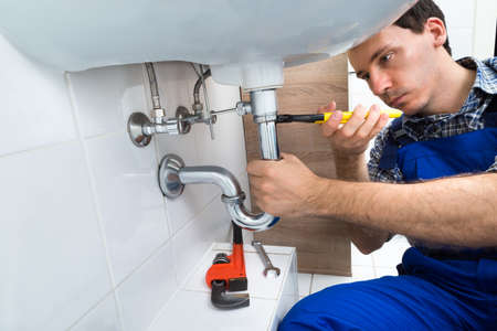 bathroom: Portrait Of Male Plumber Fixing A Sink In Bathroom
