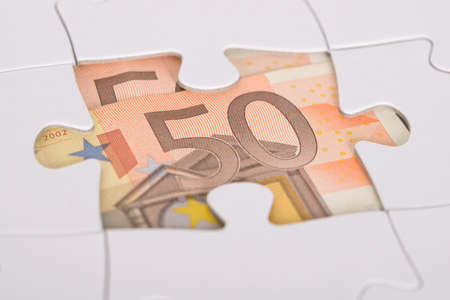 fifty euro banknote: Close-up Of Fifty Euro Banknote Hidden Under Jigsaw Puzzle Stock Photo