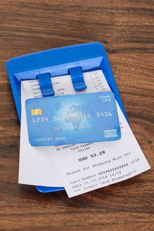 credit card bills: Close-up Of Credit Card On Shopping Receipt Over Wooden Table Stock Photo