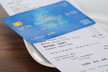 credit card payment: Close-up Of Credit Card On Shopping Receipt On Wooden Table