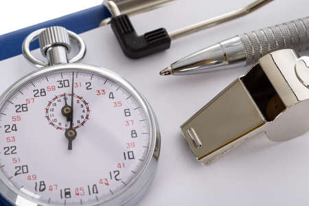 Close-up Of Clipboard With Whistle; Pen; Paper And Stopwatch On White Background