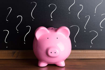 Piggy Bank In Front Of A Blackboard With Question Marks Archivio Fotografico