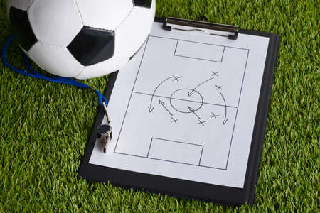 coach sport: Ball; Whistle And Soccer Tactic Diagram On Paper Over Pitch Stock Photo