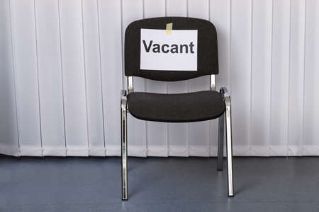 vacant sign: Office Chair With A Vacant Sign At Work Place Stock Photo