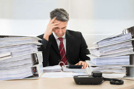 male headache: Photo Of Contemplated Businessman Working At Office