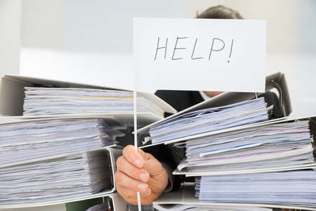 Stack Of Folders In Front Of Businessman Holding White Flag With Help Text 写真素材