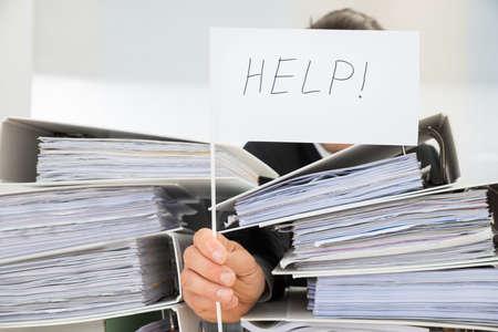 documentos: La pila de carpetas delante de hombre de negocios que sostiene la bandera blanca con texto de ayuda