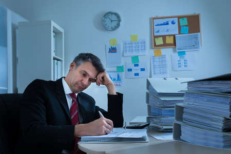 workaholic: Portrait Of Boredom Mature Businessman With Stack Of Folders Stock Photo