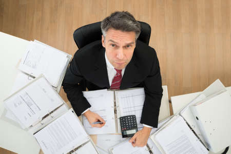 paperwork: Mature Businessman Looking Up While Doing Paperwork