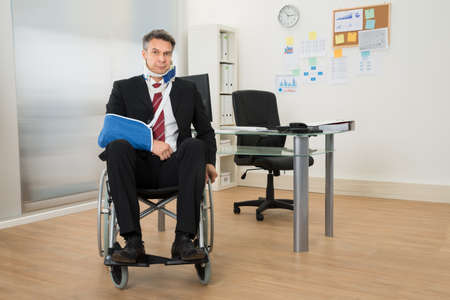 fracture arm: Portrait Of Handicapped Businessman Sitting On Wheelchair In Office