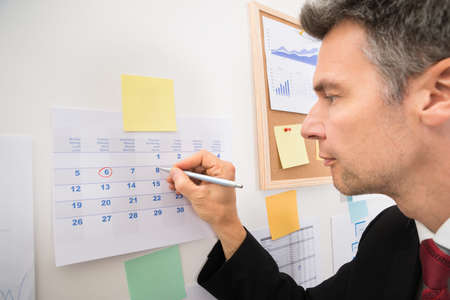 sticking: Mature Businessman Circling The Date With A Red Marker Pen On Calendar
