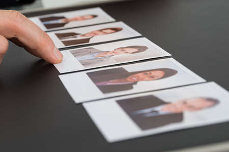executive job search: Close-up Of A Persons Hand Choosing Photograph Of A Candidate