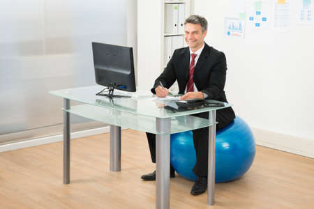 Businessman Writing On Paper Sitting On Pilates Ball In Office photo