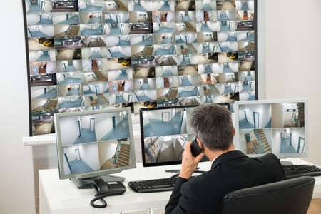 computer centre: Security System Operator Looking At Cctv Footage While Talking On Telephone Stock Photo