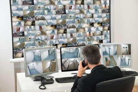 seguridad en el trabajo: Seguridad del Operador del Sistema Mirando a Cctv metraje mientras habla por tel�fono Foto de archivo