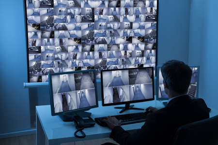Rear View Of A Man In Control Room Monitoring Multiple Cctv Footage Banque d'images