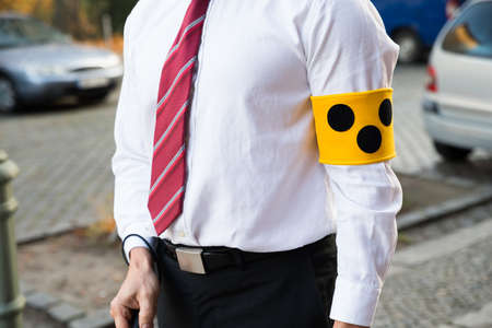 blind person: Close-up Of A Blind Person Wearing Yellow Armband
