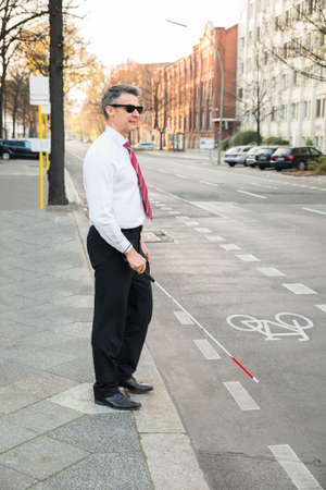 sightless: Portrait Of A Blind Mature Man Crossing Road Holding Stick Stock Photo