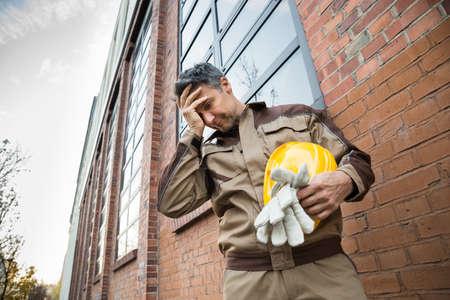 Portrait Of Rozrušený Muž dělník s přilba stojí před Brickwall