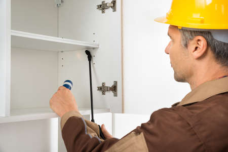 Close-up Of Pest Control Worker Wearing Hardhat Spraying Pesticides On White Shelf Stock Photo