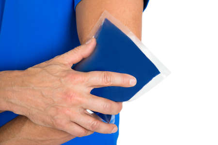 Close-up Of Hand Holding Ice Gel Pack On Elbow photo