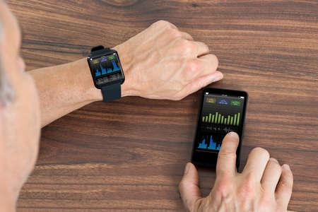 fitness men: Primer Del Hombre Maduro Con SmartWatch Y Celular Mostrando Heartbeat Tasa sentado en la mesa Foto de archivo