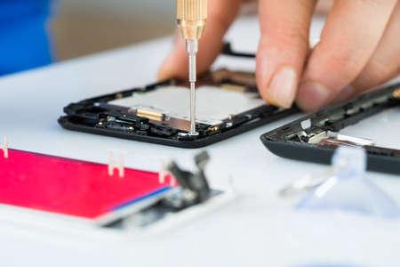 ドライバーの机の上で携帯電話を修理する人間の手のクローズ アップ