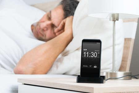 dormir: Hombre maduro que duerme en cama con la alarma en pantalla del tel�fono m�vil colocado en Mesilla de noche