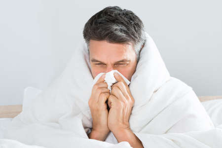 holding nose: Sick Mature Man Sitting On Bed Blowing His Nose With Handkerchief