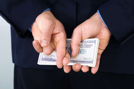 trust: Businessman Standing With Crossed Finger And Holding Banknotes Behind His Back Stock Photo